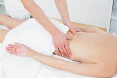 W połowie sekcja physiotherapist masowania kobiety plecy obrazy stock