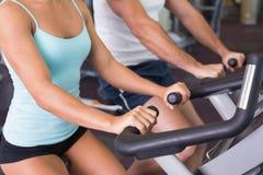 W połowie sekcja pracuje na ćwiczenie rowerach przy gym para zdjęcia royalty free