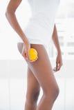 W połowie sekcja sporty kobiety mienia pomarańcze ona nogi Obrazy Stock