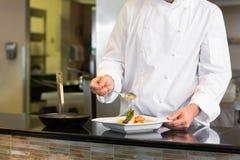W połowie sekcja szefa kuchni garnirowania jedzenie w kuchni obrazy royalty free