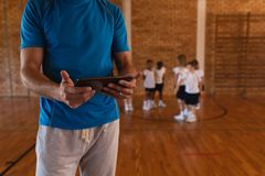 W połowie sekcja trener koszykówki używa cyfrową pastylkę przy boiskiem do koszykówki fotografia royalty free