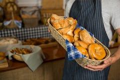 W połowie sekcja trzyma łozinowego kosz różnorodni chleby przy kontuarem męski personel Fotografia Stock