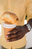 W połowie sekcja trzyma filiżankę i chleb mężczyzna Obraz Stock