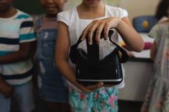 W połowie sekcja uczennicy mienia rzeczywistości wirtualnej słuchawki w sali lekcyjnej fotografia royalty free