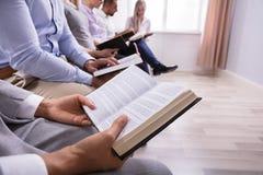 W połowie sekcja widok ludzie Czyta biblię obraz stock