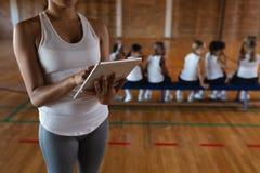 W połowie sekcji żeński trener koszykówki używa cyfrową pastylkę przy boiskiem do koszykówki fotografia stock