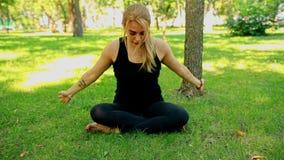 W połowie strzał młoda kobieta robi joga w parku zbiory