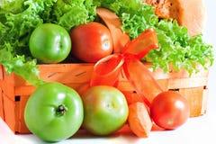 W pomarańczowym koszu zieleni pomidory Obrazy Royalty Free