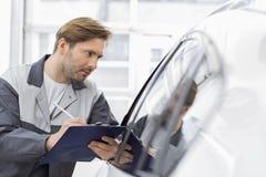 W połowie dorosły naprawy pracownika writing na schowku podczas gdy egzamininujący samochód w warsztacie Fotografia Royalty Free