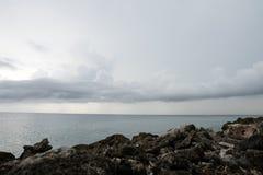 W przedpolu jest skalisty brzeg W odległości oceanie i chmurach, obrazy royalty free