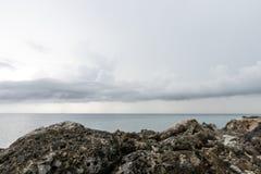 W przedpolu w ostrości jest skalisty brzeg W odległości oceanie i chmurach, obrazy royalty free