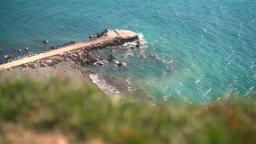 W przedpolu tam jest zielony trawa w tle tam, jest opustoszały skalisty plaża z molem na którym macha zbiory
