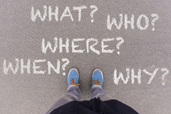 5W questions on asphalt ground, feet and shoes on floor Royalty Free Stock Images