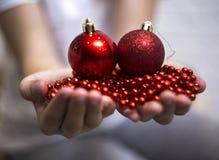 W rękach dziecko Bożenarodzeniowe piłki koraliki i boże narodzenie w nowym roku zdjęcie stock