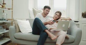 W ranek parze w piżamach w eleganckim żywym pokoju rozkazuje coś od telefonu i używa notatnika, zdjęcie wideo