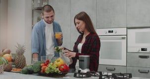W ranek parze przygotowywa wpólnie smoothie dla zdrowego śniadania w nowożytnym kuchennym projekcie, wszystkie zdjęcie wideo