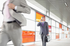 W średnim wieku biznesmen na wezwaniu podczas gdy chodzący w linii kolejowej staci Zdjęcie Stock