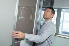 W średnim wieku biznesmen patrzeje out biurowego okno Fotografia Stock