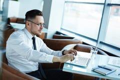 W średnim wieku biznesmen pracuje na laptopie Fotografia Royalty Free