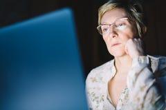 W średnim wieku kobieta pracuje na laptopie Zdjęcia Stock