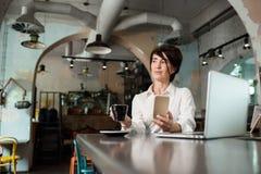 W ?rednim wieku kobieta siedzi w kawiarni, pije kaw? i pracuje przy komputerem, Kobieta trzyma telefon obraz stock