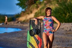 W ?rednim wieku kobieta z czerwonym w?osy stoi na piaskowatej pla?y i trzyma surfboard fotografia stock