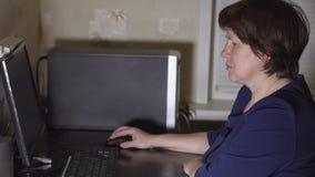 W średnim wieku kobiety obsiadanie przy komputerem przed okno Zdjęcia Stock