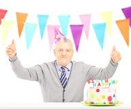 W średnim wieku mężczyzna świętuje jego urodziny daje aprobatom Zdjęcia Stock