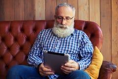 W średnim wieku mężczyzna z pastylka komputerem osobistym Fotografia Royalty Free