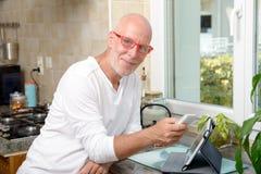 W średnim wieku mężczyzna z telefonem komórkowym Fotografia Stock
