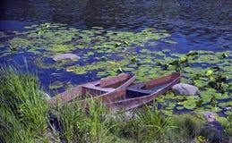 W rzece, dwa łodzi tonęli wśród liści grążel Obraz Stock