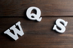 W, S and Q letters white wooden letters on dark wooden background Royalty Free Stock Photos