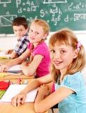 W sala lekcyjnej dziecko w wieku szkolnym obsiadanie. zdjęcia stock
