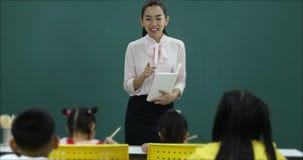 W sali lekcyjnej, Azjatycki nauczyciel uczy ucznia zdjęcie wideo