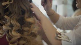 W salonie fryzjer czesze wielkich kędziory na ona długie włosy zdjęcie wideo