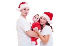 W Santa kapeluszach szczęśliwa rodzina zdjęcia royalty free