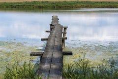 Wąski drewniany footbridge nad stawowa woda Obrazy Royalty Free