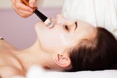 w spa Piękna kobieta z twarzową maską przy piękno salonem Fotografia Stock