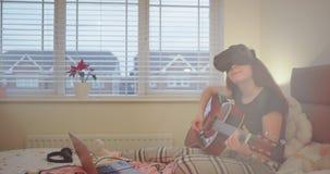 W sypialnia nastolatka dziewczynie bawić się na gitarze i używa VR w tym samym czasie, szczęśliwy ona cieszy się czas zbiory