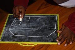 W szkole podstawowej, obrazek ono rysuje na łupku z kredą fotografia stock