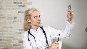 W szpitalu Kobieta doktorski radiolog patrzeje xray wizerunek czaszka w białym medycyna mundurze 4K zbiory