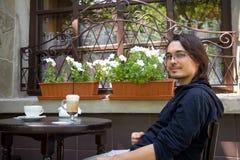 W tarasowej kawiarni ładny młody obsiadanie obrazy royalty free