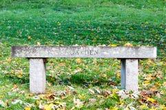 W trawie ogrodowa ławka Obrazy Stock