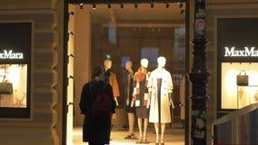 W wieczór ulica iść młoda dziewczyna z plecakiem i przychodzi okno butik MaxMara zbiory