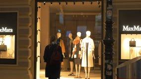 W wieczór ulica iść młoda dziewczyna z plecakiem i przychodzi okno butik MaxMara zbiory wideo