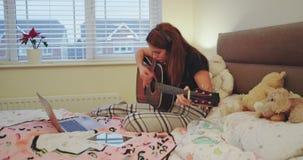 W wygodnej sypialni młodej damie bawić się w gitarze bardzo skoncentrowanej, używać notatnika w tym samym czasie, ona zbiory wideo