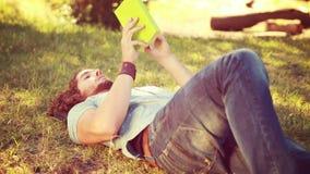 W wysokiej jakości 4k formata młodego człowieka czytelniczej książce w parku zdjęcie wideo