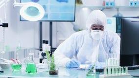 W zaawansowanym biochemii laboratorium naukowiec w coveralls robi notatkom zbiory wideo