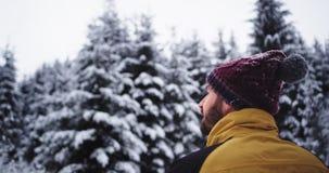 W zadziwiającym śnieżnym lesie z dużym drzewnym młodym turystą cieszy się widok wokoło on podczas gdy pije niektóre gorących napo zbiory wideo
