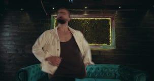 W zadziwiającym ciemnym wewnętrznym fachowym tancerza tanu przed kamerą obracającą z jego z powrotem zdjęcie wideo